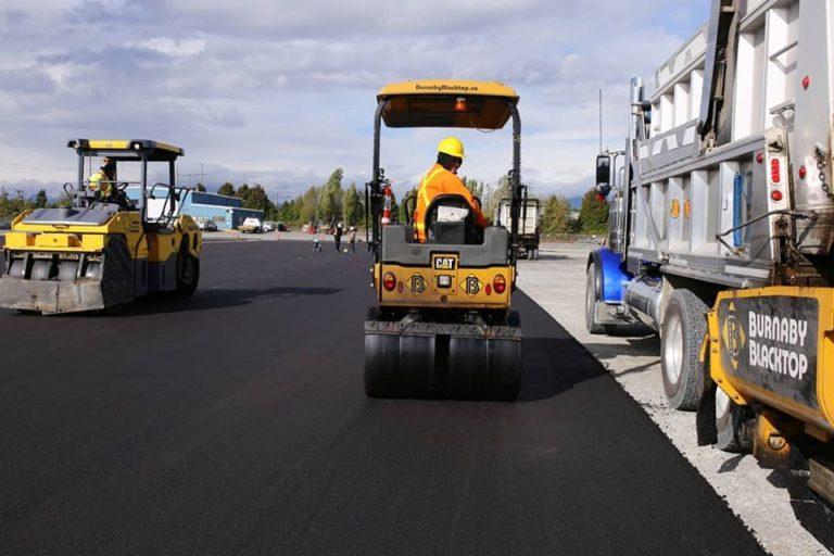 two pavers laying asphalt